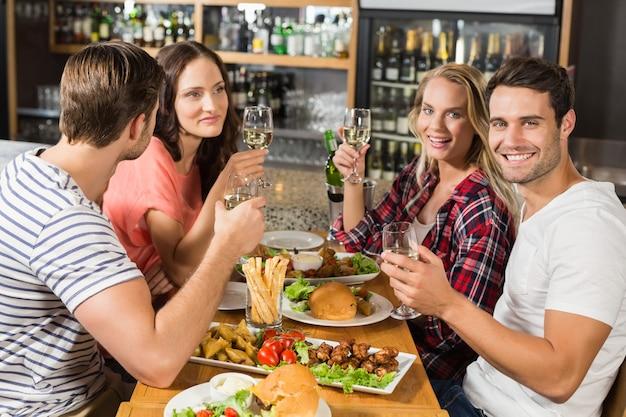Amigos brindando con vino blanco