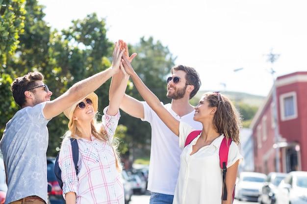 Amigos de la cadera haciendo high-five en la ciudad.
