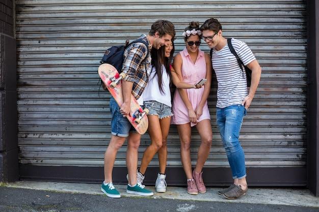 Amigos de la cadera mirando el teléfono inteligente y apoyados contra la puerta rodante