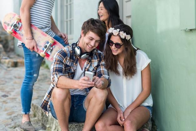 Amigos de la cadera mirando el teléfono inteligente y sentado en los pasos en la ciudad
