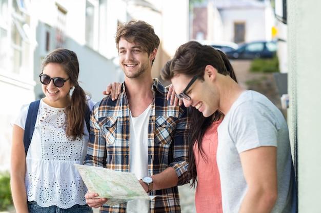 Amigos de cadera revisando el mapa en la ciudad.