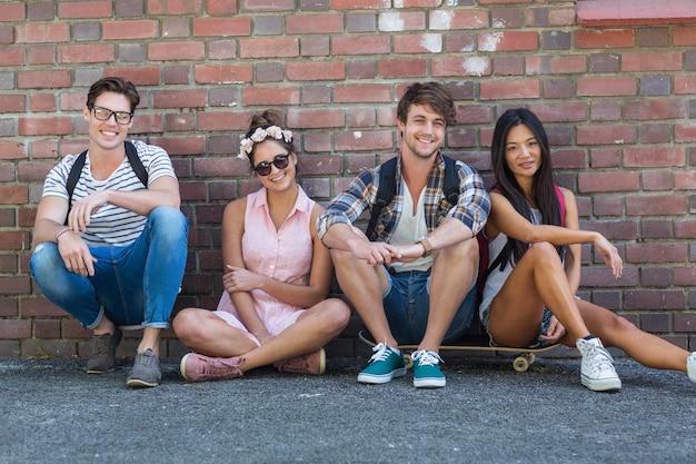 Amigos de cadera sentados en el piso contra la pared en la calle