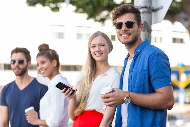 Amigos de la cadera sonriendo a la cámara en la ciudad.