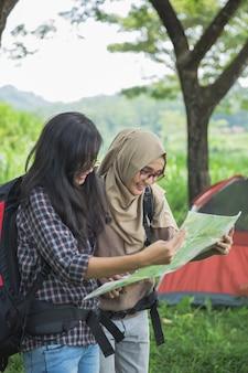 Amigos caminando en actividades de verano al aire libre usando el mapa