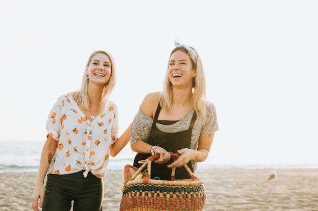 Amigos caminando en la playa con una cesta de picnic