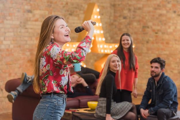Amigos cantando al karaoke en una fiesta