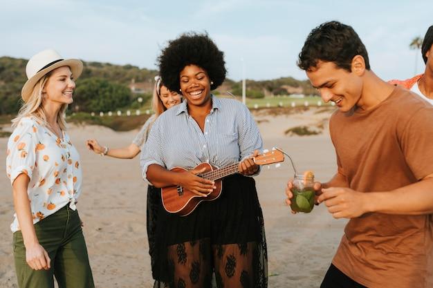 Amigos cantando y bailando en la playa.