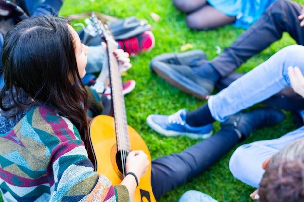 Amigos cantando canciones en el parque divirtiéndose juntos