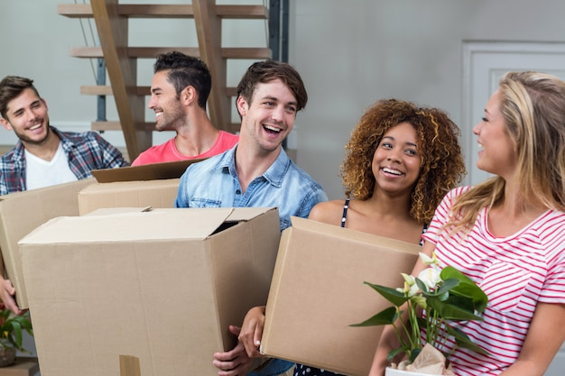 Amigos cargando cajas mientras se mudan a una casa nueva