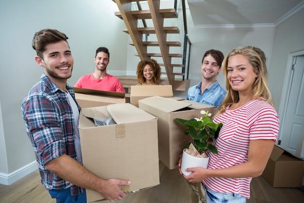 Amigos cargando cartón mientras se traslada a una casa nueva