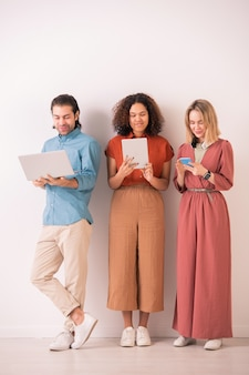 Amigos casuales jóvenes felices con computadora portátil, tableta digital y teléfono inteligente de pie junto a la pared y mirando a través de publicaciones en las redes sociales