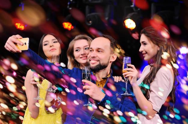 Los amigos celebran el evento, ríen, bailan y beben champán.