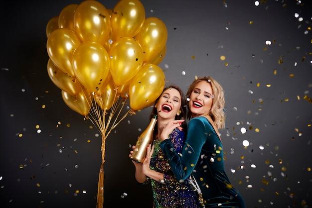Amigos celebrando el año nuevo entre confeti cayendo