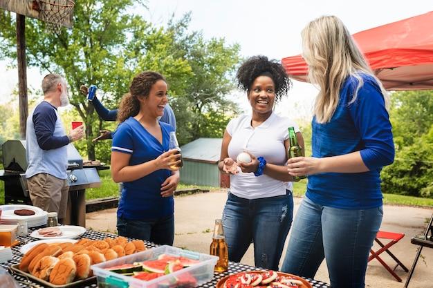 Amigos celebrando y comiendo en una fiesta en el portón trasero