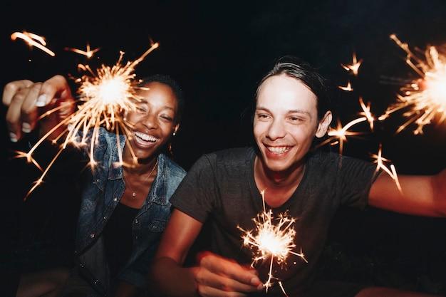 Amigos celebrando con bengalas en la noche