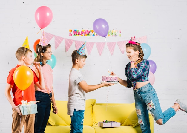Amigos celebrando cumpleaños de niña con pastel