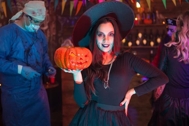 Amigos celebrando halloween con aspecto de monstruos aterradores. chica sosteniendo una calabaza y mirando a la cámara.