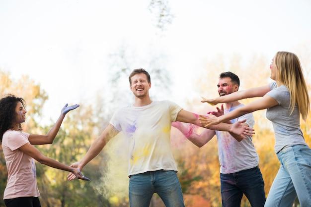 Amigos celebrando holi en la naturaleza