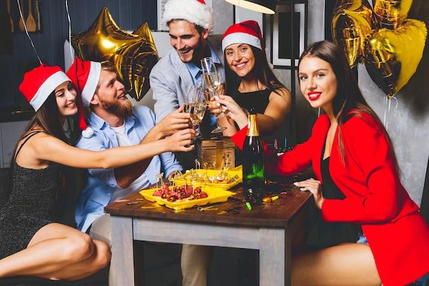 Amigos celebrando la víspera de navidad o año nuevo. mesa de fiesta con champagne
