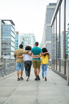 Amigos cercanos caminando juntos por la ciudad