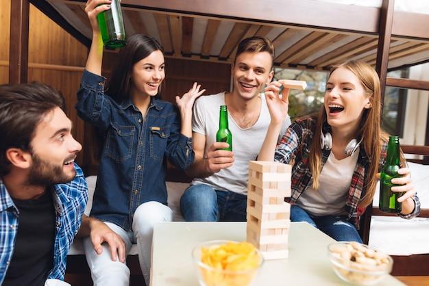 Amigos cercanos felices y sonríen jugando en jenga.