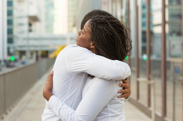 Amigos cercanos multiétnicos con camisas blancas, abrazándose afuera
