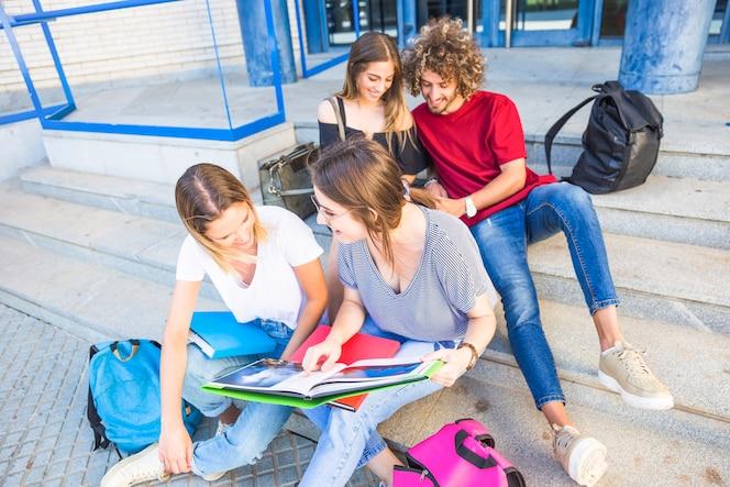 Amigos charlando y estudiando en las escaleras de la universidad