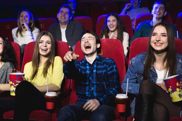 Los amigos de un chico y una chica se ríen a carcajadas en una sala de cine.