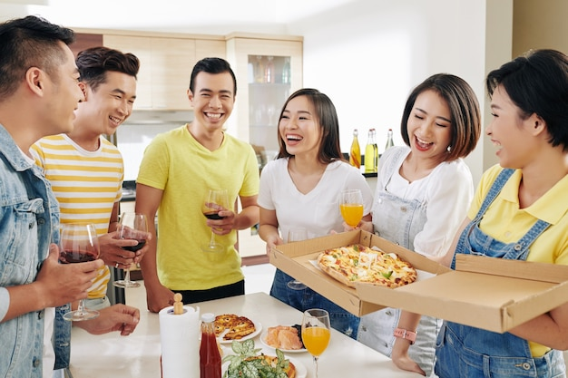 Amigos comiendo y bebiendo en la fiesta en casa