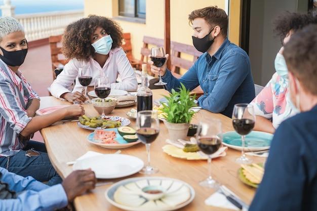 Amigos comiendo y bebiendo vino junto con máscaras protectoras