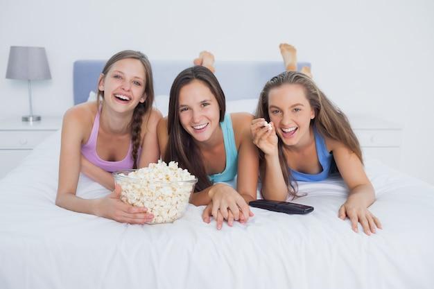 Amigos comiendo palomitas de maíz y viendo la televisión