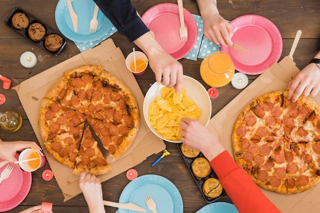 Amigos comiendo pizza en una fiesta