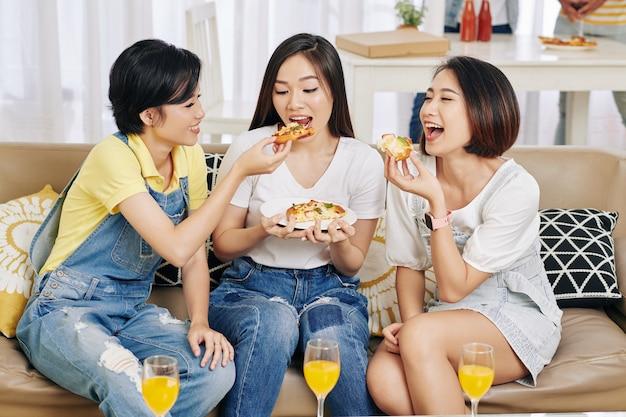 Amigos comiendo pizza en la fiesta