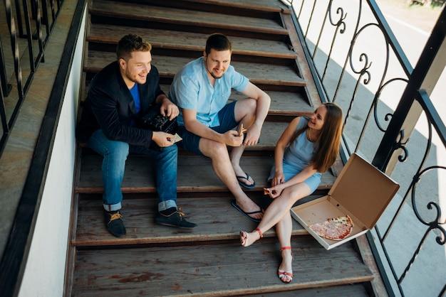 Amigos comiendo pizza juntos en los escalones de la casa