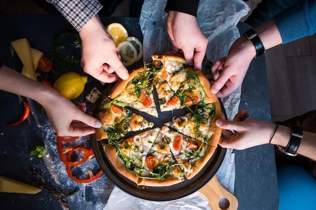 Amigos comiendo pizza. las manos de la gente agarrando una rebanada de pizza.