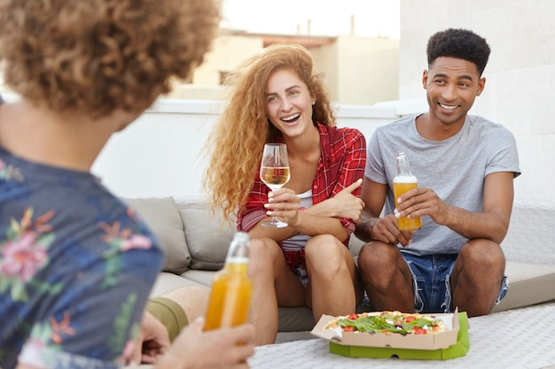 Amigos comiendo pizza sabrosa y divirtiéndose mientras charla