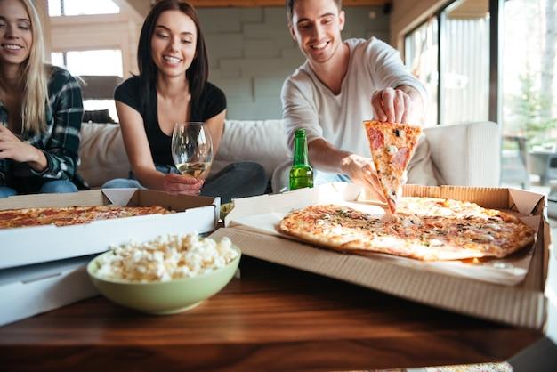 Amigos comiendo sabrosa pizza en casa mientras hacen una fiesta