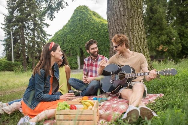 Amigos, comunicación. dos jóvenes chicos alegres con guitarra y bonitas novias sentadas en una manta bajo un árbol hablando de picnic en un día cálido