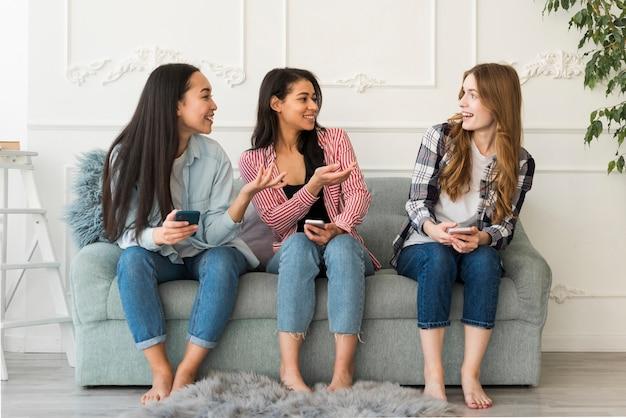 Los amigos se comunican sentados en el sofá.