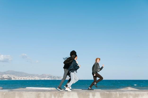 Amigos corriendo enfrente del mar