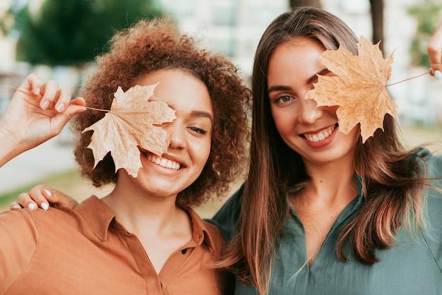 Amigos cubriendo sus ojos con una hoja seca