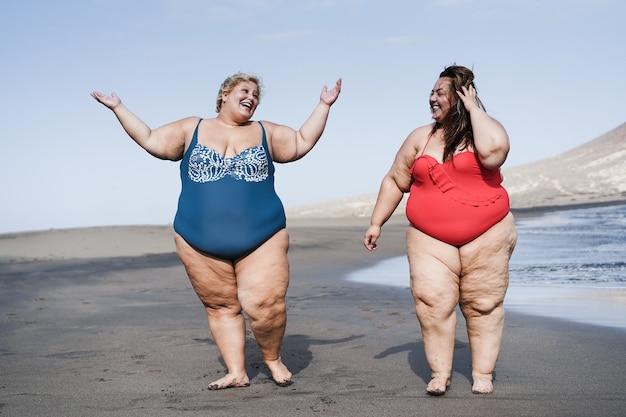 Amigos con curvas divirtiéndose en la playa durante las vacaciones de verano - centrarse en las caras