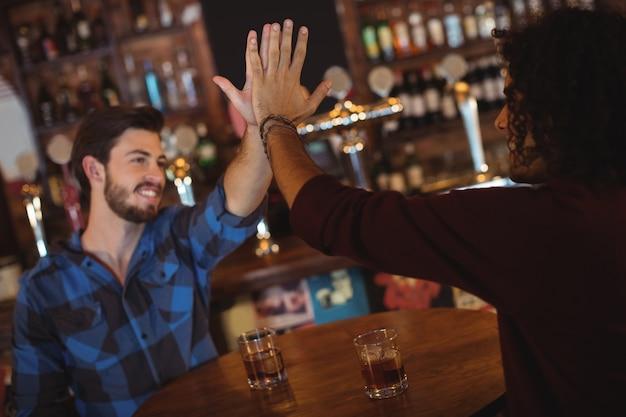 Amigos dando cinco mientras beben