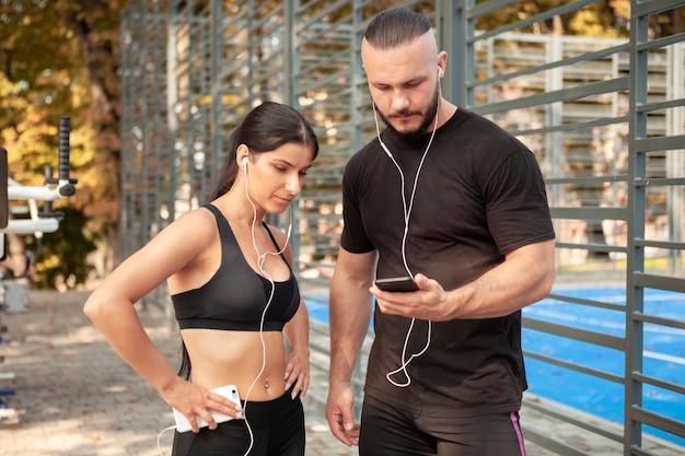 Amigos deportivos con móviles y auriculares.