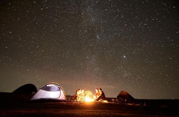 Amigos descansando junto al campamento, fogata bajo el cielo estrellado de la noche