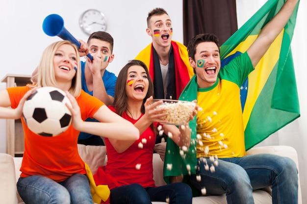 Amigos de diferentes naciones celebrando el gol del equipo favorito.