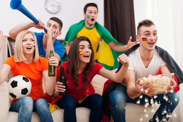 Amigos de diferentes naciones que apoyan al equipo de fútbol.