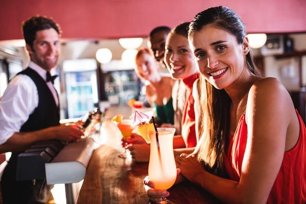 Amigos disfrutando de bebidas en barra de bar en discoteca