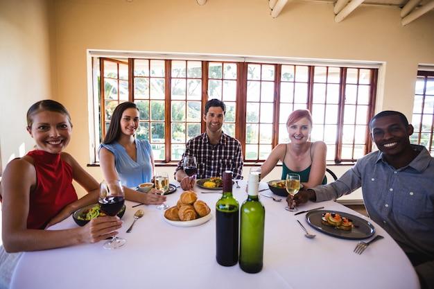 Amigos disfrutando de comida y vino en la mesa en el restaurante