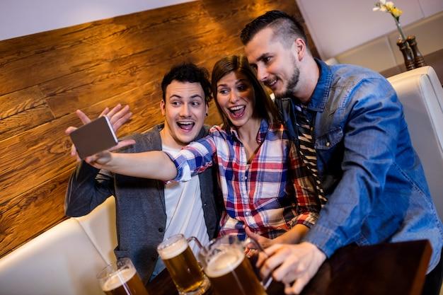 Amigos disfrutando mientras toman selfie en restaurante